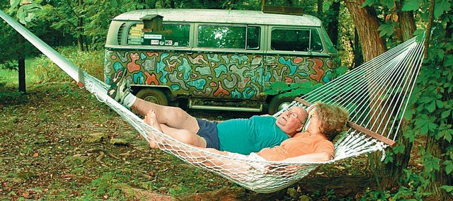 The Schmiedelers relax in a hammock next to an old Volkswagen bus that's part of a collection of found objects that adorn their backyard in rural Johnson County.