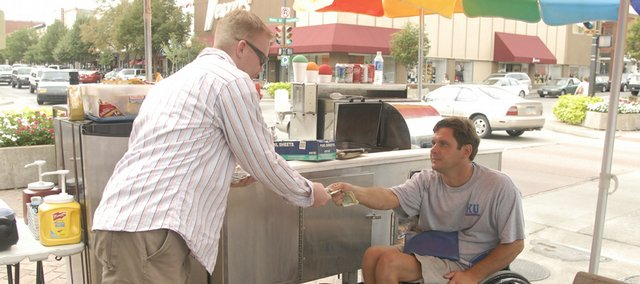 "Craig Nowatzke, right, owner of ""SunDog,"" an outdoor food cart, makes change for Jon Klassen, Lawrence, Friday in downtown Lawrence. Four of five city commissioners support the idea of raising the sales tax to provide a new multimillion dollar revenue source for the city."