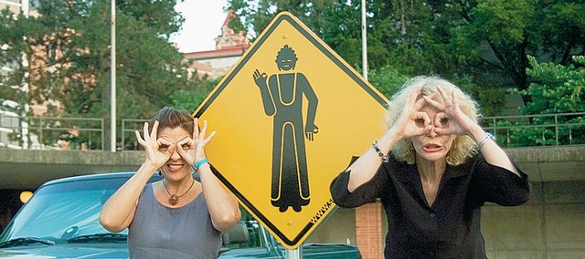 "Lawrence artists Maria Velasco, left, and Janet Davidson-Hues goof off near one of the ""way-finding"" signs designed to lure viewers inside the Spencer Museum of Art for an audio installation called ""Stop // Look // Listen,"" which opens Thursday."