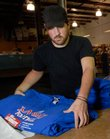 Harold Fatzer, a shirt catcher at Midwest Graphics, 4811 Quail Crest Place, organizes freshly inked and dried Kansas University football T-shirts. The company is in the process of printing 25,000 T-shirts for Saturday's home opener for the Jayhawk football team. KU officials expect at least 44,000 fans at the game against Central Michigan.