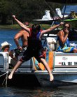 Tammi Weems, center, and Easton Weems, 7, bottom right, both of Ozawkie, watch 12-year-old Levi Saving, of Baldwin City, jump into the water while their boat is anchored in Party Cove at Perry Lake in this file photo from September 2007.