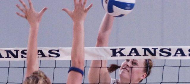 Kansas University's Caitlin Mahoney, center, sends a spike back at UMKC's Jamie Hagerman. The Jayhawks swept the Kangaroos on Tuesday in Horejsi Center.