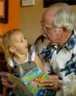 Lawrence resident Chuck Benedict, 81, reads to his one-year-old great granddaughter Finley LaDuke on Friday at their home. Two years ago Benedict moved in with his granddaughter Sarah LaDuke and her husband, Aaron LaDuke. Benedict explained that he has cherished the time he has spent with them.