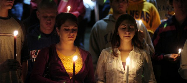 Kansas University freshmen, from left, Chris Hall, Arkansas City, and Bridgette Moen and Erica Henderson, both of Fredonia, share a quiet moment with other students and community members during a candlelight vigil Monday at KU's Wescoe Beach in remembrance of the lives lost on Sept. 11, 2001. The event was organized by the KU Young Democrats, KU College Republicans and KU Collegiate Veterans Association.