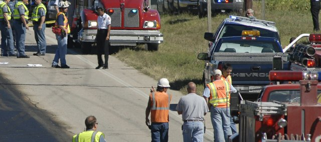Area emergency personnel work the scene of a hit-and-run accident where two construction workers on U.S. Highway 59 were killed Sept. 11 between North 800 and 900 roads at Pleasant Grove. Construction crews had been repaving the road.