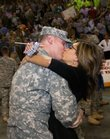 Cherry Jordon, of Lawrence, far right, greets her husband, Cpt. Matthew Jordon, with a kiss Friday, Sept. 14, 2007 during a welcome back ceremony for the Kansas National Guard at the Kansas Expocentre in Topeka. On the left, Todd Loughney, of Topeka, gets a look at his 3-month-old son, Keagan Loughney, with his wife, Karma Loughney. Approximately 220 members of the Kansas National Guard were welcomed back Friday.