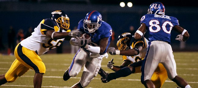 Kansas receiver Aqib Talib cuts between Toledo defenders Douglas Westbrook , left, and Barry Church as he catches a block from receiver Dezmon Briscoe following a reception in the first half against Toledo, Saturday, Sept. 15, 2007 at Memorial Stadium.
