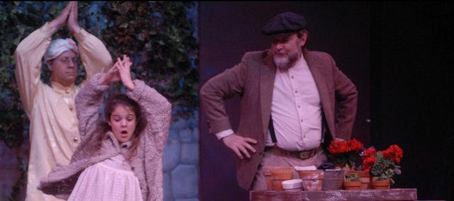 "Richard Walker (Fakir), left, dances with Sally Spurgeon (Mary Lennox) while Jeff Blair (Ben the gardener) looks on during rehearsal Monday for ""The Secret Garden."" In the musical adapted from the beloved children's book, Mary rejuvenates a secret garden and, in the process, heals herself and members of her family."