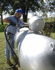 Dan Miller, salesman and deliverer for Heetco of Lawrence, prepares to fill a propane tank at a resident south of Lawrence Wednesday, Sept. 26, 2007. While the news isn't too bad for natural gas users, propane users can expect an increase in their gas costs this winter.