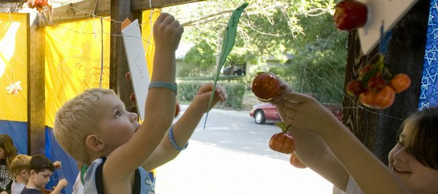 Members of the Lawrence Jewish Community Center hang decorations in a booth on Sunday in preparation for the Jewish holiday of Sukkot. Sukkot is a fall harvest festival during which a structure is built in historical recognition of ancestral Jews who dwelled in temporary shelters. Sukkot precedes another day of rejoicing, called Simchat Torah, which falls on Wednesday for reform Jews and Thursday for Orthodox Jews.