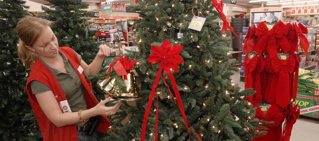 Whitney Baker, Lawrence, a floor sales associate at the Westlake Ace Hardware store, 711 W. 23rd St., decorates a Christmas tree display in the store Tuesday evening, Oct.. 9, 2007. Just a few days after Columbus Day retailers across the country are already offering Christmas items for sale.