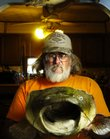 """Hoyt resident Michael Corrigan is no stranger to the world of handfishing, otherwise known as """"noodling."""" Here he shows off the head of a 70-pound flathead he caught three years ago on the Red River in Oklahoma."""