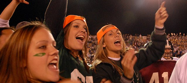 Free State fans Brooke Abney, center, and Jenna Brantley, left, celebrate last season's 49-15 victory against Lawrence High. The Firebirds and Lions will renew their rivalry tonight.