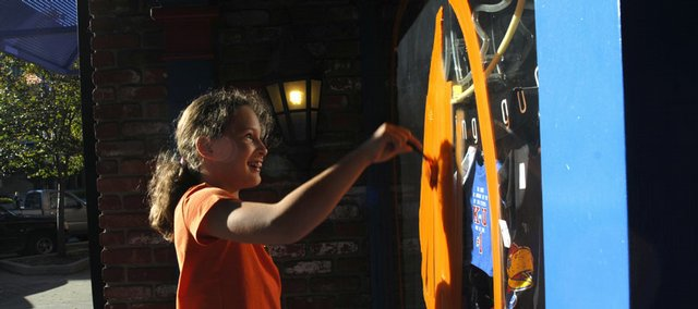 Reagan Ingram, 9, paints a pumpkin on the Jock's Nitch Sporting Goods window Saturday at 837 Mass. About 50 painters participated in the 36th annual Halloween Paint-In.