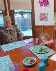"Meredith Cummings, 5, center, finishes up her broccoli while sitting near an enlarged ""Flat Daddy"" photo of her father, Maj. Brent Cummings, who is serving a 15-month tour with the 216th Infantry in Baghdad through May. In the kitchen is Meredith's mother, Laura Cummings, her older sister, Emily, 8, and their dog Travis. The Cummingses, of Manhattan, enlarged a photo their father sent from Iraq and had it made into a Flat Daddy in February."