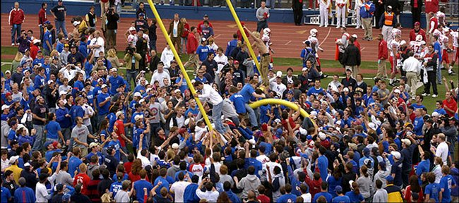 Jayhawk fans storm the field in this Journal-World file photo to tear down the goal posts after Kansas' 40-15 win over Nebraska at Memorial Stadium in 2005.