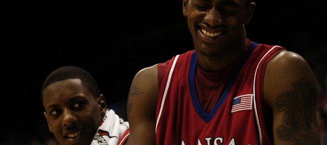 Kansas forward Darrell Arthur, right, and guard Mario Chalmers have a laugh on the bench in the second half. Arthur had a game-high 20 points in the Jayhawks' 93-56 exhibition rout Tuesday of Fort Hays State in Allen Fieldhouse.