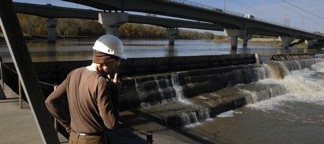 Brian Farley, plant manager for the Bowersock Power Co., looks out at the Kansas River as it flows over the Bowersock Dam on Thursday. Inspections of the dam, which was built in the 1870s, are done mostly by feel because the river is so muddy. But city leaders would like to get a good look at it now because a new report by a city-hired engineering firm says there is reason to be concerned about the dam's future.