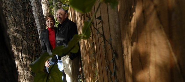 Sheryl and Robert Jacobs say the shrubs, trees and vines planted along their fence help tie it in with the rest of their Vermont Street yard. Lawrence landscapers recommend placing curved beds along fence lines and painting or staining fences to make them less abrupt.