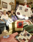 Judy Johanning, center, Baldwin City, has made and gathered more than 40 quilts to take to tornado-ravaged Greensburg for the holiday season. Displaying some of the quilts Tuesday with Johanning are members of the Maple Leaf Quilters Guild, Wincel Jehle, Baldwin, left, and Cathy Miles, Lawrence, right. The quilts will be delivered Nov. 30 at the Kiowa County Hospital in Greensburg.