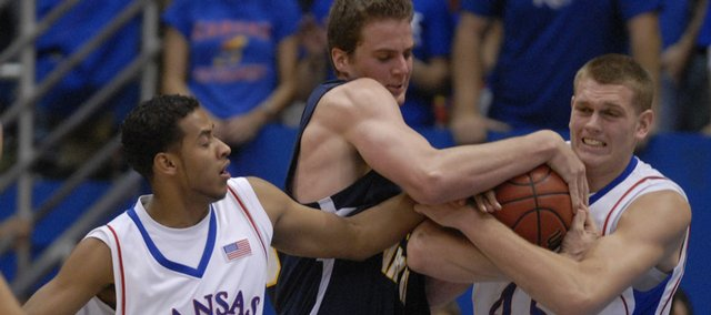 Kansas guard Jeremy Case, left, and center Cole Aldrich, right, try to wrestle the ball away from Northern Arizona center Kyle Landry. Tenacious defense lifted the Jayhawks to an easy 87-46 victory Wednesday over the Lumberjacks at Allen Fieldhouse.