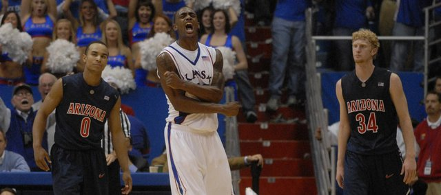 Kansas University's Darrell Arthur, center, lets out a scream as the Jayhawks pulled away from Arizona. At left is UA's Jerryd Bayless, while Chase Budinger is at right. Arthur led KU with 20 points in a 76-72 overtime victory Sunday at Allen Fieldhouse. Bayless and Budinger combined for 46 points.