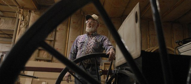 Don Werner, co-owner of Werner Wagon Works near Horton, both restores old wagons and makes new ones. He's pictured in his shop through the wheel of one of his creations.