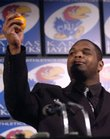 Kansas University senior defensive lineman James McClinton, of Garland, Texas, raises his orange in recognition to the Jayhawks' receiving an Orange Bowl bid at during a press conference Hadl Auditorium in this file photo. McClinton bit into the orange, saying that was his reaction to learning they got an Orange Bowl bid. It is the first time in KU history that the football team has been selected to participate in a Bowl Championship Series game.