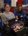 Jock's Nitch employees, from left, Amie Worthington and Kelsey Allen quickly fold some of the T-shirts that became available Monday for Kansas University's Orange Bowl appearance Jan. 3 in Miami. To get to the game, some travel packages cost $2,000.