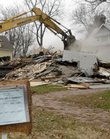 A worker for R.D. Johnson Excavating Co. of Lawrence demolishes the house at 1200 N.Y. Neighbors bought the house, which was in disrepair and was the site of frequent police visits.