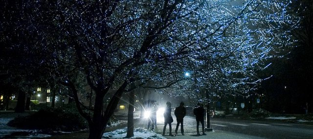 Kansas University students make their way down Jayhawk Boulevard under the glow of the icy trees lining the walkway Monday on the KU campus.