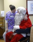 Kristina Emerson, activity coordinator at Brandon Woods Retirement Community, sits on the lap of Santa, played by Larry Kline, as resident Aloha Rizzo waits for her turn. Kala Garber, 10, watches.