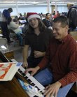 Josh Longbottom, left, and Kim Manz, both of the Plymouth Congregational Church of Lawrence, sing carols and play the piano Thursday during a Christmas party at the Lawrence Interdenominational Nutrition Kitchen, 221 W. 10th St. About 170 people attended the annual event.