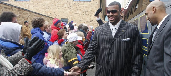 Kansas University defensive tackle Jamal Greene slaps hands with fans as he prepares to board a charter bus headed for Forbes Field. The Jayhawks received the royal treatment from fans on Thursday morning as they left Lawrence en route for Miami, where they will take on Virginia Tech in the Orange Bowl on Jan. 3.