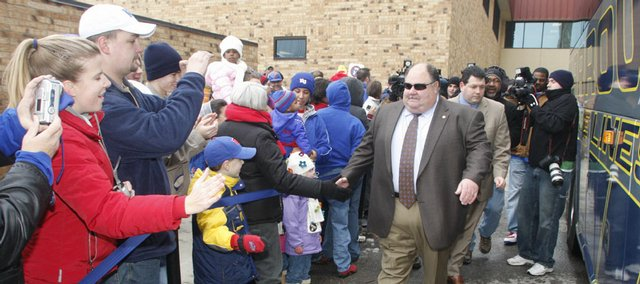 Kansas University Head Football Coach Mark Mangino slaps hands with Jayhawk fans as he boards a bus outside Allen Fieldhouse. The Jayhawks took the bus to Forbes Field in Topeka, then flew to Florida, where they will take on Virginia Tech on Jan. 3 in the Orange Bowl. Hundreds of fans braved frigid morning temperatures to send the team off Thursday.