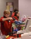 Target employee Judy Grammer, left, scans an item while returning and exchanging products for guests at the store, 3201 Iowa. As gift card use increases, the number of returns has been dropping over the past few years.