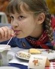 Hazel Ingram, 8, of Lawrence, sips tea with a straw Friday, Dec. 28, 2007 during the Lawrence Public Library Children's Tea Party at the library, 707 Vermont St. The holiday party's theme was western.