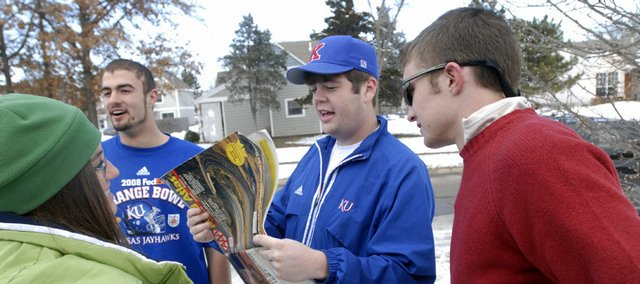 Kansas fans, from left, Laura Boddington, Topeka, KU freshman Chance Riley, junior Tim Burgess and sophomore Stewart Bell, all of Lawrence, check an atlas before leaving Sunday to watch the Jayhawks in the Orange Bowl in Miami.