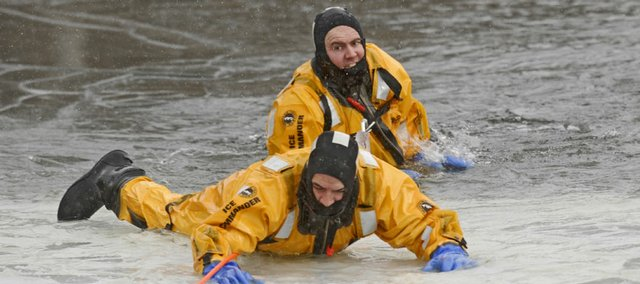 Lawrence-Douglas County Fire & Medical's Troy Gourley, foreground, is helped out of frigid water and onto a sheet of ice by Lt. John Mathis on Friday at the West Campus Pond at Kansas University. The department conducted ice rescue training as part of its annual training exercises.
