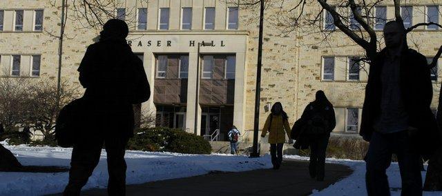 Students mill around Fraser Hall on the Kansas University campus.