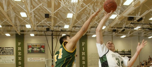 Free State's Weston Wiebe (34) attempts a layup over Shawnee Mission South's Sida Niu on Friday at FSHS.  Wiebe was fouled on the play. The Firebirds won, 53-52.