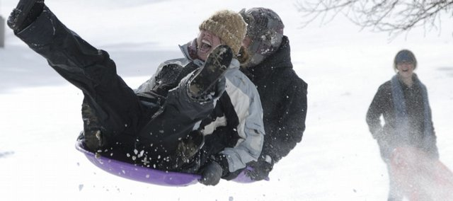 Two KU students hang on to their sled as they catch some air over a bump on slopes Wednesday near Potter Lake. Overnight snowfall in Lawrence led to the cancellation of KU classes and local schools.