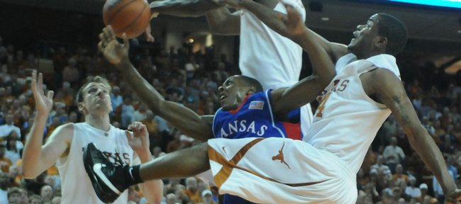 Kansas guard Mario Chalmers, center, is mobbed by Texas defenders Connor Atchley, left, Damion James, top, and Justin Mason on an attempted layup. The Longhorns beat the Jayhawks, 72-69, Monday in Austin, Texas.