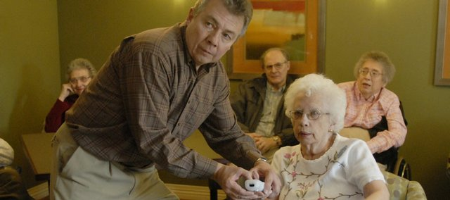 Kim Blocher, left, social programming director at Brandon Woods Retirement Community, assists Natalie Gump, 81, with a new Nintendo Wii system, which the residents used Friday for bowling. The therapeutic value of the virtual game system is being touted in retirement centers across the nation.