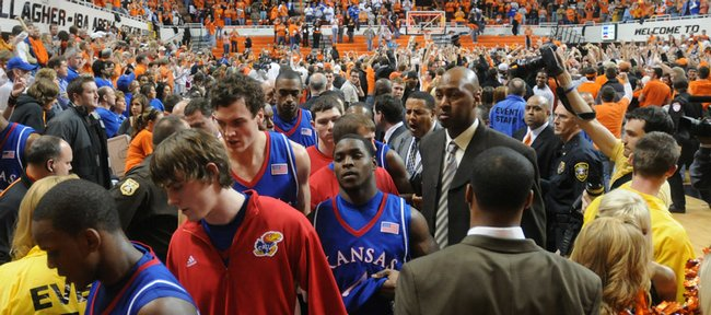 A morose bunch of Jayhawks makes its way from the court through a sea of celebrating Oklahoma State fans. OSU stunned the Jayhawks, 61-60, on Saturday in Stillwater, Okla.