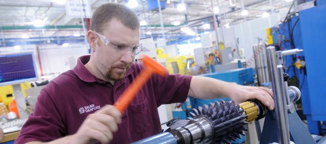 Brad Ballard works on a gear cutter on the machine floor Wednesday at Sauer-Danfoss in the East Hills Business Park. Sauer-Danfoss, which makes transmissions, is participating in the Douglas County Manufacturing Certificate Program, which combines education and real-world experience to help give workers a leg up in the industry.