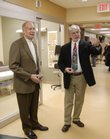 Dr. Scott Robinson, center, medical director of Lawrence Memorial Hospital's emergency department, gives a tour of the new Simons Center for Emergency Medicine to David Ambler, left, and Roger Morningstar. The center, which was dedicated Tuesday, features 26 patient rooms and two resuscitation/trauma rooms.