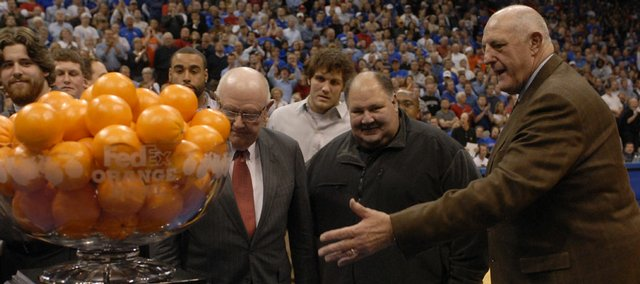 Kansas University Chancellor Robert Hemenway, left, Head Football Coach Mark Mangino, and Athletic Director Lew Perkins surround the Orange Bowl trophy at midcourt during a halftime recognition ceremony for the football team at Allen Fieldhouse in this file photo from 2008.