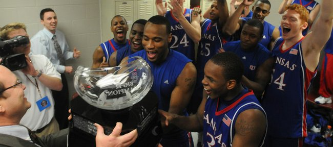 The Kansas University's men's basketball team receives the Big 12 Conference championship trophy from league commissioner Dan Beebe, left. KU's 72-55 victory over Texas A&M on Saturday in College Station, Texas,