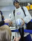 Jayhawk guard Mario Chalmers signs an autograph for Jaclyn Honn, 5, Shawnee, Tuesday as the Kansas University men's basketball players loaded a bus at Allen Fieldhouse. The Jayhawks hit the road Tuesday for Omaha, Neb., and their first-round game in the NCAA Tournament with Portland State on Thursday.